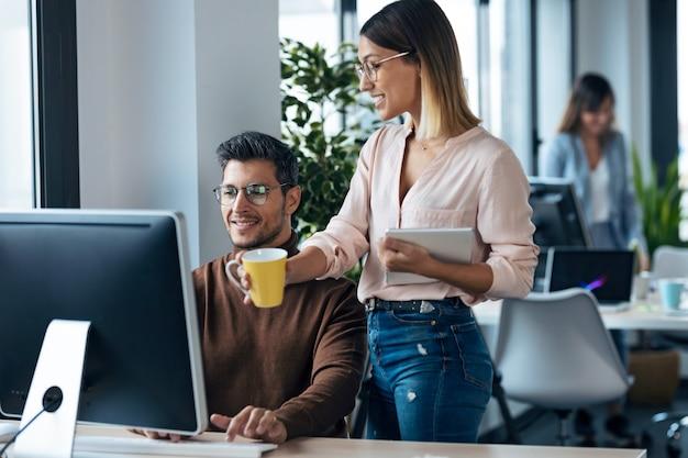 Photo de deux jeunes collègues travaillant avec un ordinateur et une tablette numérique dans un espace de travail moderne. concept de remue-méninges.