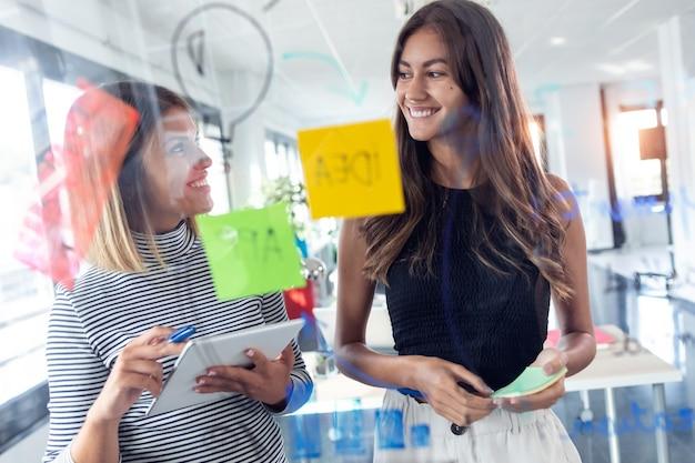 Photo de deux jeunes femmes d'affaires travaillant ensemble sur du verre mural avec des autocollants post-it dans le bureau de démarrage moderne.