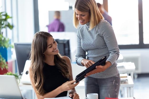 Photo de deux jeunes femmes d'affaires travaillant avec une tablette numérique dans le bureau de démarrage moderne.