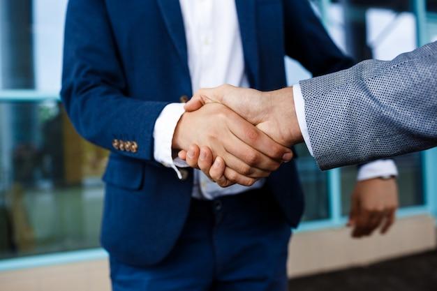 Photo de deux jeunes hommes d'affaires dans la rue se serrant la main