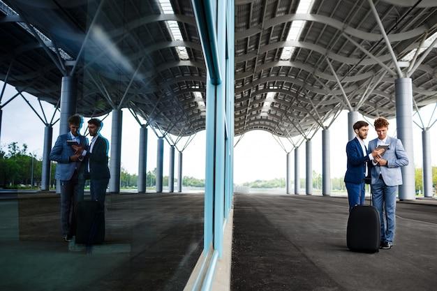 Photo de deux jeunes hommes d'affaires parlant sur la station et tenant la tablette reflétée dans la fenêtre