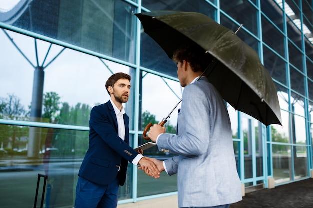 Photo de deux jeunes hommes d'affaires réunis à la gare