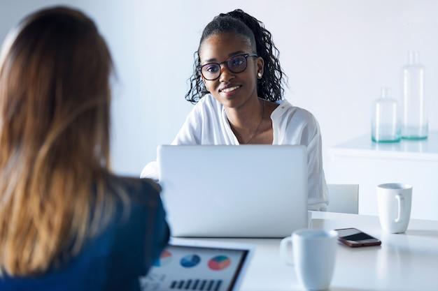 Photo de deux jolies jeunes femmes d'affaires travaillant avec une tablette numérique et un ordinateur portable au bureau.