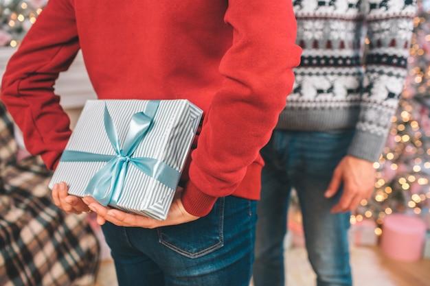 Photo de deux personnes debout l'une en face de l'autre. l'homme en pull rouge détient la boîte avec le présent derrière. les gens le cachent.