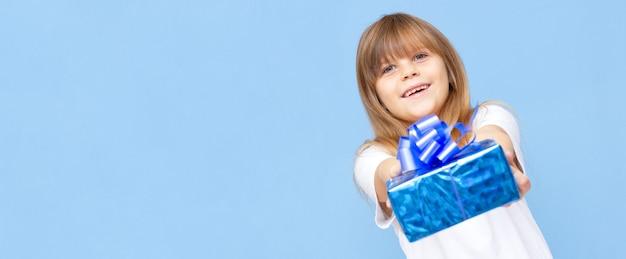 Photo d'une douce écolière mignonne portant un t-shirt blanc souriant tenant une boîte présente bleue isolée fond de couleur bleue bannière copie espace