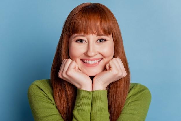Photo de douce jeune femme avec un sourire rayonnant isolé sur fond bleu
