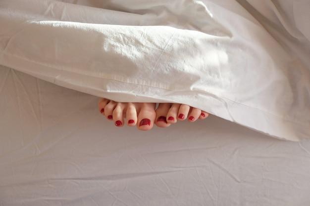 Photo douce des pieds de la femme sous une couverture, point de vue de dessus. pédicure rouge