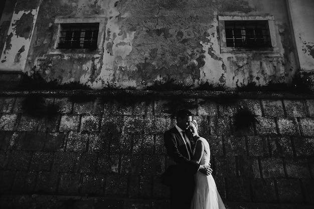 Photo dramatique en noir et blanc d'un couple de mariage posant devant un mur de pierre