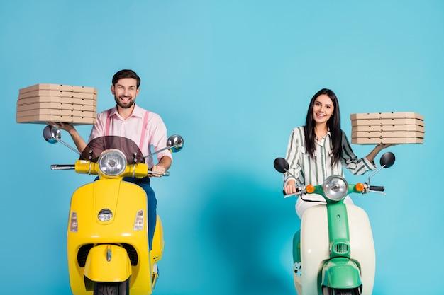 Photo de drôle belle dame guy conduire deux vélomoteur vintage transporter des boîtes à pizza en papier coursier occupation frais jonque fastfood tenues de soirée isolé mur de couleur bleu