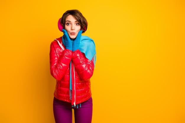 Photo de drôle de charmante dame envoi de baisers aériens main dans la main sur les pommettes jeune millénaire porter pardessus rouge décontracté gants bleus pantalon violet
