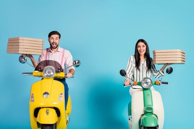 Photo de drôle de dame excité guy conduire deux vélomoteur vintage transporter des boîtes à pizza en papier profession de courrier rapide jonque livraison de restauration rapide tenue de soirée isolé mur de couleur bleu