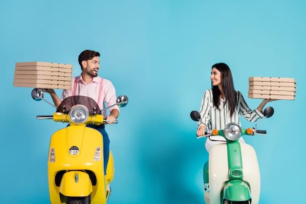 Photo de drôle de dame guy conduire deux vélomoteur rétro vintage transporter des boîtes à pizza en papier occupation de messagerie fastfood look yeux bonne humeur tenue de soirée isolé mur de couleur bleu
