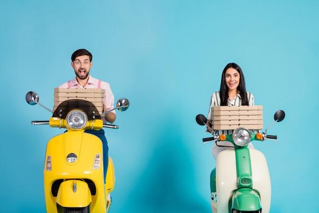 Photo de drôle excité lady guy bonne humeur conduire deux vélomoteur vintage transporter des boîtes à pizza en papier occupation de messagerie livraison rapide tenues de soirée isolé mur de couleur bleu