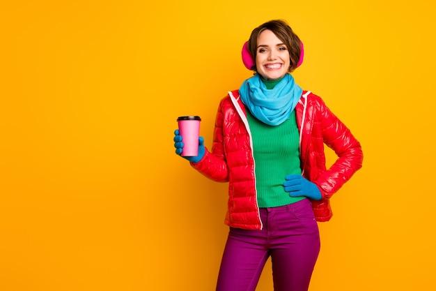 Photo de drôle jolie dame tenant une tasse de papier café à emporter chaud journée froide boisson énergétique porter manteau rouge décontracté écharpe bleue gants couvre-oreilles pantalon