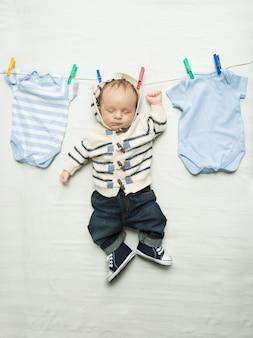 Photo drôle de mignon petit garçon accroché sur une corde à linge