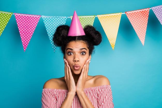 Photo de drôle de peau foncée choquée dame bras pommettes fête d'anniversaire inattendue porter un chapeau de cône chemise rayée blanche rouge épaules nues drapeaux en pointillés colorés pendent sur le mur bleu
