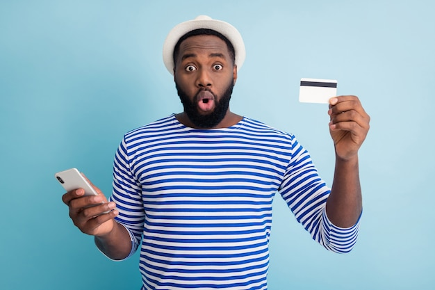 Photo de drôle de peau sombre guy voyageur tenir téléphone app navigation faire des achats en ligne utiliser cool service carte de crédit porter chapeau de soleil blanc chemise de marin rayé mur de couleur bleu isolé