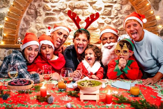 Photo drôle de selfie de grande famille de plusieurs générations avec des chapeaux de père noël s'amusant à la fête de noël