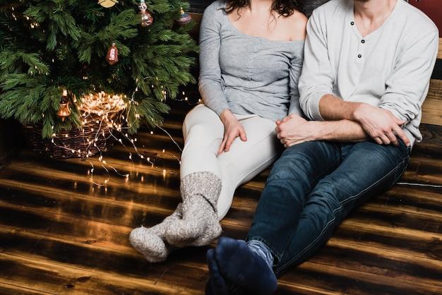 Photo du bas de l'arbre de noël et des jambes dans des chaussettes chaudes