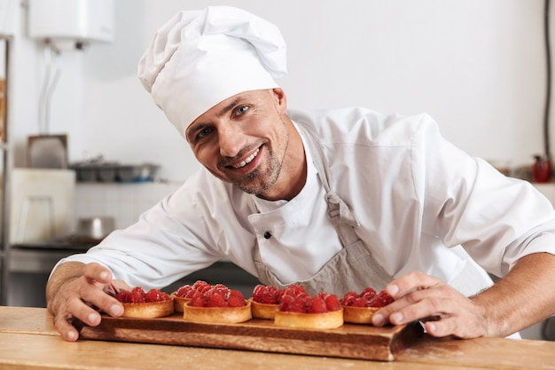 Photo du chef masculin heureux en uniforme blanc tenant la plaque avec des gâteaux