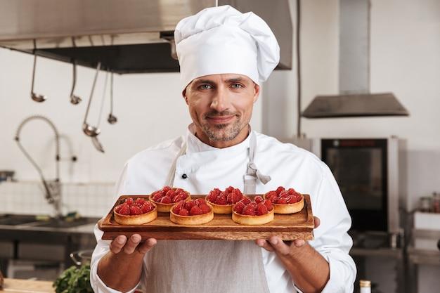 Photo du chef de sexe masculin adulte en uniforme blanc tenant la plaque avec des gâteaux