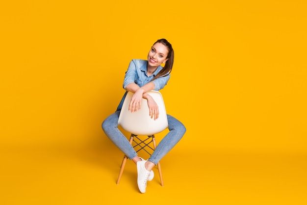 Photo du corps entier d'une belle fille séduisante qui a fière allure à huis clos, sourire à pleines dents, assis sur une chaise blanche isolée sur fond de couleur vive