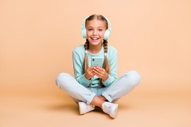 Photo du corps entier de la belle petite dame drôle écouter écouter la chanson des écouteurs bonne humeur s'asseoir les jambes de plancher croisées porter des chaussures de jeans pull bleu isolé mur de couleur beige