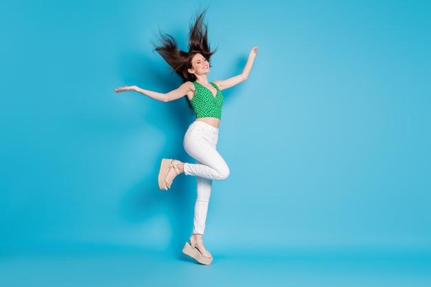 Photo du corps entier d'un contenu candide charmante fille sauter profiter de la coupe de cheveux de la mouche de l'air coup tenir les mains lever porter des chaussures de tenue de bonne apparence isolées sur fond de couleur bleu