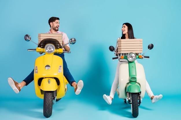 Photo du corps entier de drôle de dame guy conduire deux cyclomoteurs rétro vintage transporter des boîtes à pizza en papier occupation de courrier regard yeux bonne humeur tenue de soirée isolé mur de couleur bleu