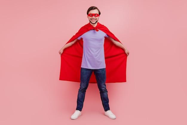 Photo du corps entier du jeune superman fort pouvoir porter un masque de manteau confiant isolé sur fond de couleur rose