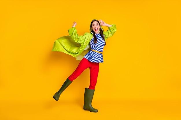 Photo du corps entier d'une fille enthousiaste profitez de la saison du printemps pour se réjouir de la marche des pluies, portez un bon look, un manteau de chaussures en gomme isolé sur un fond de couleur brillant