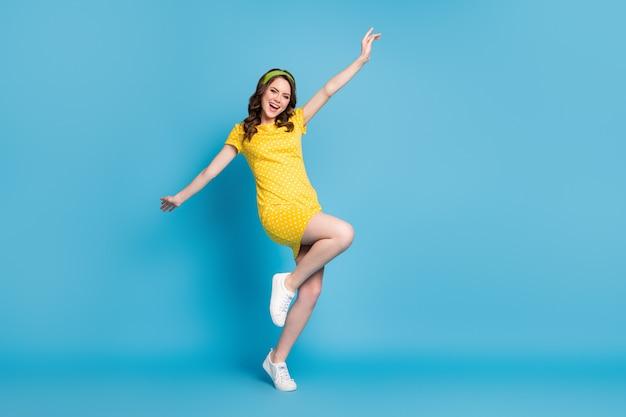 Photo du corps entier d'une fille excitée profitant d'une jambe de main levée isolée sur fond de couleur bleu
