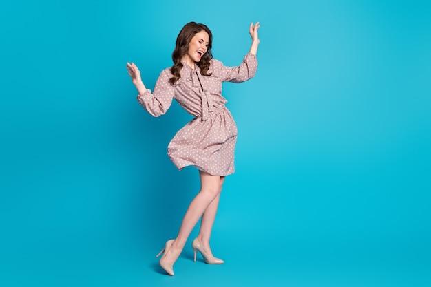 Photo du corps entier d'une fille folle au contenu candide profitez de la danse de joie lever les mains porter des vêtements de bonne apparence chaussures isolées sur fond de couleur bleu