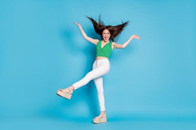 Photo du corps entier d'une fille folle et candide profitez de la coupe de cheveux pour se réjouir de la mouche de l'air porter un singulet blanc isolé sur fond de couleur bleu