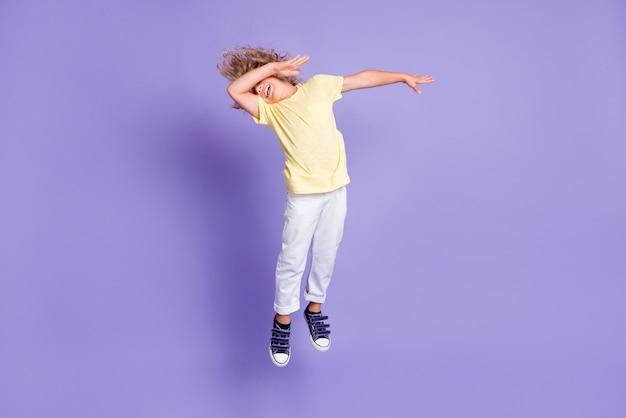 Photo du corps entier d'un petit enfant dabber sauter près du visage des bras porter un pantalon de t-shirt jaune blanc isolé sur fond de couleur violet