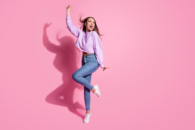 Photo du corps entier de profiter de la fille se réjouir avoir du temps libre regarder copyspace lever la main porter des baskets à la mode pull lilas mouche des cheveux isolée sur fond de couleur pastel