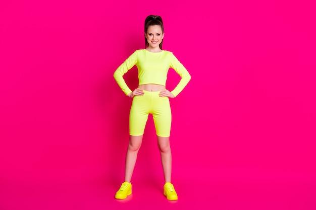 Photo du corps entier d'une sportive confiante mettant les mains à la taille isolée sur fond de couleur rose brillant