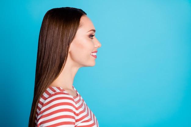 Photo du côté du profil d'une jolie fille séduisante ayant l'air de bonne humeur copyspace profitez d'écouter un ami porter une chemise de style décontracté isolée sur fond de couleur bleu
