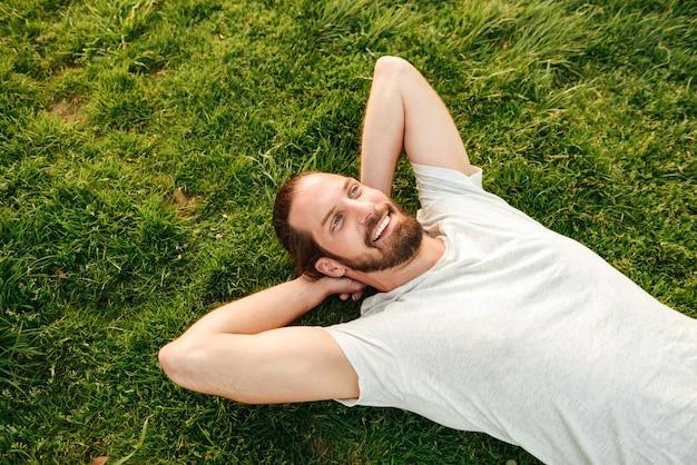 Photo du haut de sourire bel homme vêtu d'un t-shirt blanc, passer du temps libre dans un parc verdoyant allongé sur l'herbe et mettre les mains derrière le dos
