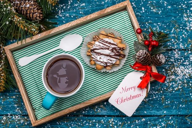 Photo du nouvel an de thé avec bonhomme de neige, gâteau sur table avec des branches d'épinette, cartes postales avec souhait de noël