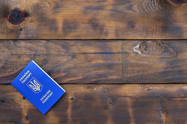 Photo du passeport étranger ukrainien, posé sur une surface en bois sombre. le concept d'introduction de l'exemption de visa pour les citoyens ukrainiens