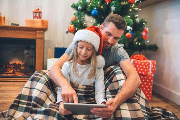 Photo du père assis avec sa fille et en regardant tablette.