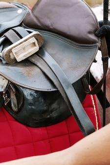 Photo du processus de préparation à l'équitation - un tapis de selle rouge, sur lequel une selle en cuir a été placée. l'aile de la selle est relevée, vous pouvez également voir les étriers et harnais rentrés