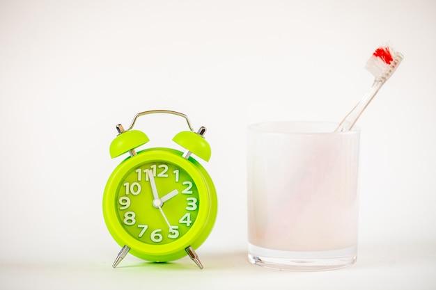 Une photo du réveil vert et de la brosse à dents. il est temps de nettoyer les dents. soins dentaires, photo de concept d'hygiène personnelle. un rappel important pour les enfants et les adultes de prendre soin de leurs dents.