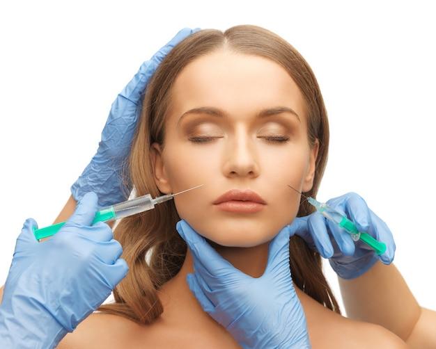 Photo du visage de la femme et des mains de l'esthéticienne avec une seringue