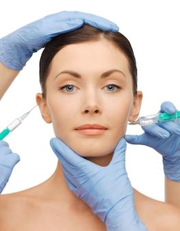 Photo du visage de la femme et des mains de l'esthéticienne avec des seringues