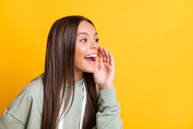 Photo d'une écolière drôle et délicate portant une tenue grise décontractée, la bouche du bras dit un fond de couleur jaune isolé secret