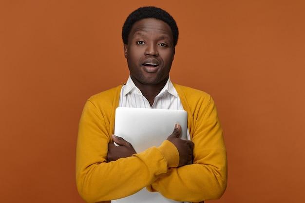 Photo de l'élégant jeune gestionnaire à la peau sombre en cardigan jaune tenant un ordinateur portable générique, quittant le bureau après le travail. personnes, technologie moderne, travail, profession et concept de gadgets électroniques