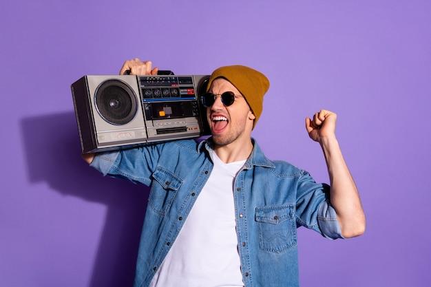 Photo de l'élégant à la mode joyeux amateur de musique criant extatique dansant avec une basse forte tenant un enregistreur avec les mains isolées sur fond de couleur vive violet