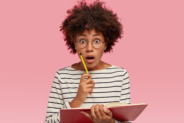 Photo d'une élève étonnée qui regarde avec surprise, a ouvert la bouche, entend des nouvelles choquantes, écrit des informations dans l'organisateur